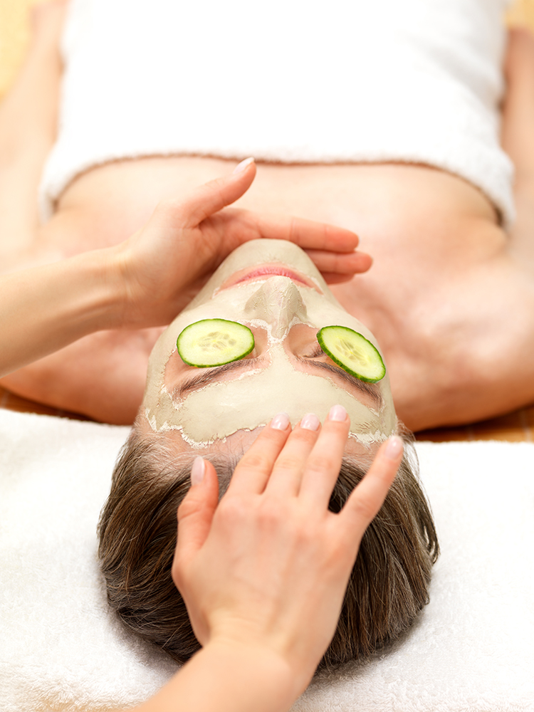 Woman wearing facial mask and cucumber slices on eyes at spa